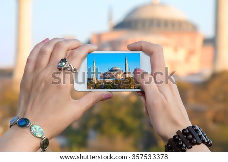 Woman taking Photo with camera phone in Istanbul city female hands with fashion bracelets  holding white telephone with Picture of famous attraction view
