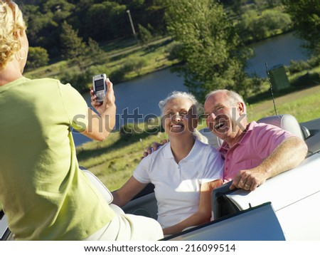 Woman taking photograph of senior couple by river