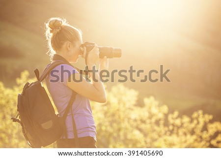 Woman taking photos outdoors on a sunny evening - stock photo