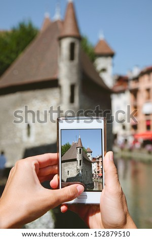 Woman taking photos with mobile phone. Taking photos with phone in Annecy streets, France. - stock photo