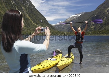 Woman taking picture of man raising kayak oar over head on shore of mountain lake - stock photo
