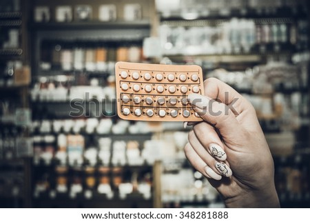 woman taking pill out from blister pack at pharmacy. toned photo - stock photo