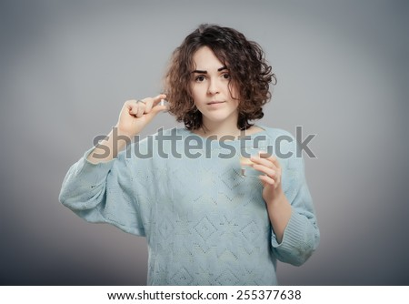 Woman taking pills. Depressed young woman taking a pill while standing against grey background - stock photo