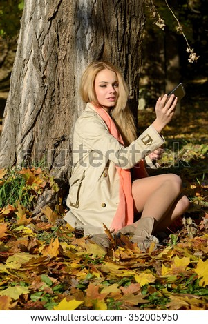 Woman taking self photos in a park with smart phone while sitting next to a tree
