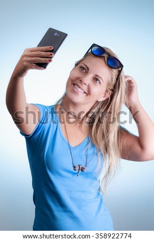 Woman taking self portrait with smartphone. Wearing blue shirt and blue sunglasses on a blue background
