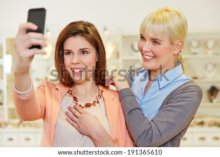 Woman taking selfie at jewelry store while trying on a necklace - stock photo