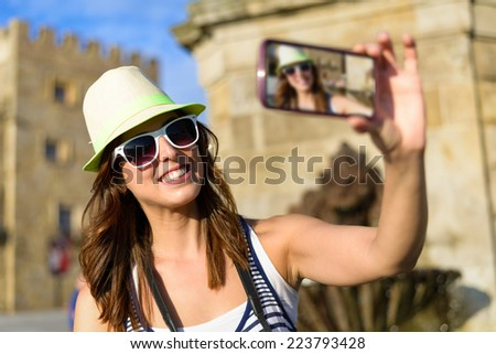 Woman taking selfie photo on summer vacation travel visiting typical spanish landmark in Asturias. Female tourist in Plaza Marques and Revillagigedo Palace , Gijon, Spain. - stock photo