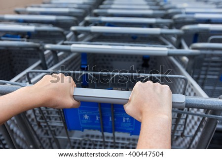 Woman taking shopping cart near supermarket. Closeup on female hands holding shop trolley