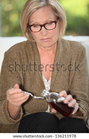 Woman taking syrup - stock photo