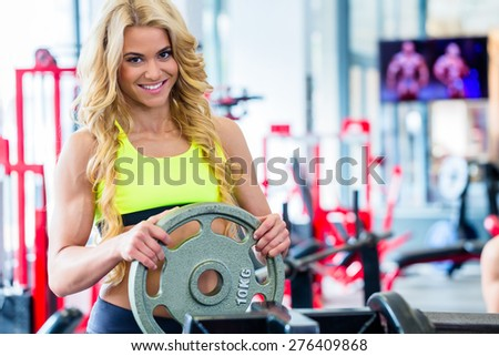 Woman taking weights from stand in fitness gym preparing for training - stock photo
