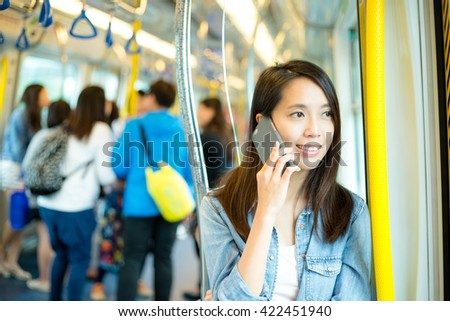 Woman talk to mobile phone in train compartment at hong Kong - stock photo