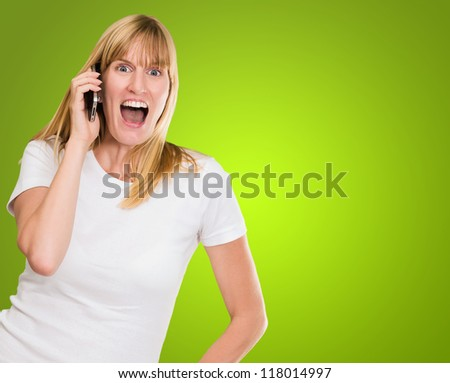 Woman Talking On Cell Phone against a green background