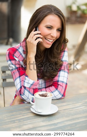 Woman talking on cell phone at cafe - stock photo