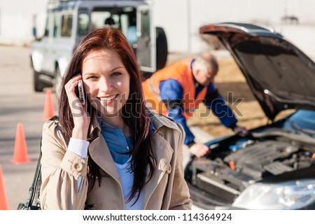 Woman talking on cellphone after car breakdown trouble problem mechanic - stock photo