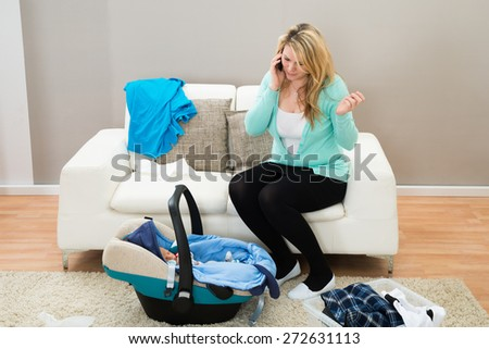 Woman Talking On Mobile Phone With Laundry Clothes In Living Room
