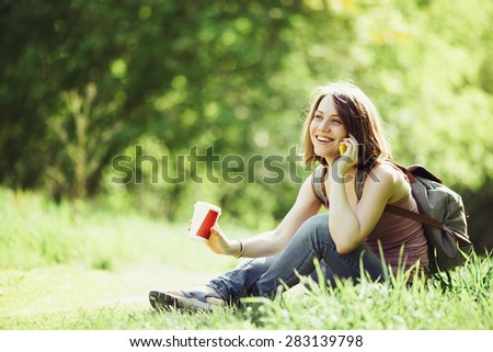 Woman talking on smartphone and having coffee in a park. Wearing casual outfit with backpack. Vintage toned.