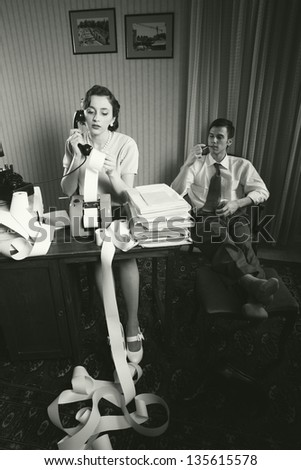 Woman talking on the phone calculating and analyzing financial reports, businessman relaxed in chair - stock photo