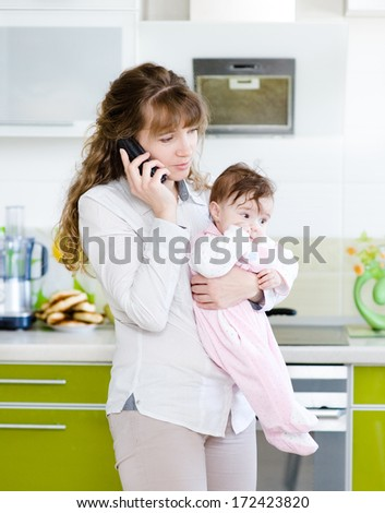 woman talking on the phone while holding her baby in her arms in the kitchen - stock photo