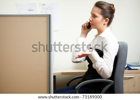 Woman talking over the phone in the office - stock photo