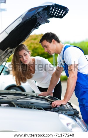 Woman talking to a car mechanic in a parking area, both are standing next to the car - stock photo