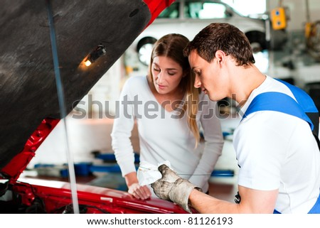 Woman talking to a car mechanic in his repair shop, both are standing next to the car