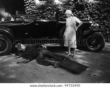 Woman talking to man working on car - stock photo