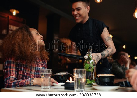 Woman talking to waiter at restaurant. Young woman sitting at cafe with waiter standing by smiling. - stock photo
