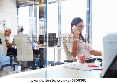 Woman talking using phone at her desk in an office - stock photo