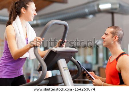 Woman talking with a personal trainer while exercising on a treadmill - stock photo