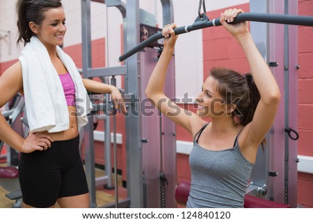 Woman talks to friend using weight machine in gym