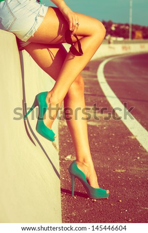 woman tan legs in high heel green shoes outdoor shot  summer day - stock photo