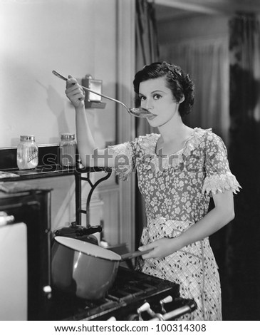 Woman tasting food cooking on stove - stock photo