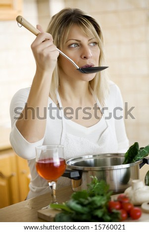 woman tasting the food she is cooking - stock photo