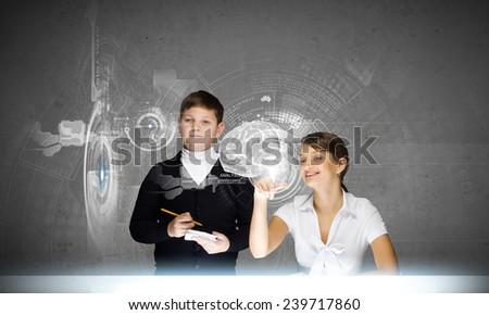 Woman teacher and boy at lesson touching media screen