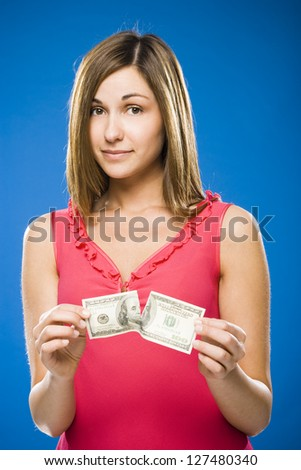 Woman tearing American hundred dollar bill