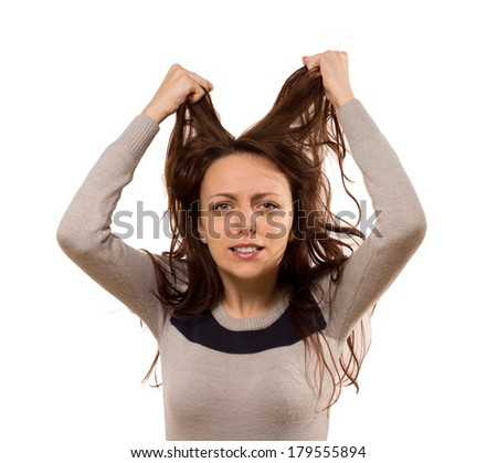Woman tearing at her hair in desperation and frustration while gnashing her teeth at the camera, isolated on white - stock photo