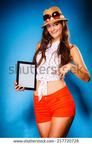 Woman teen girl showing blank copy space screen of tablet touchpad computer on blue. Electronic technology. - stock photo