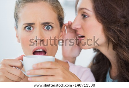 Woman telling secret to her friend and astonishing her while drinking coffee - stock photo