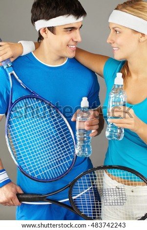 Woman tennis player standing with water bottle and embracing her male colleague