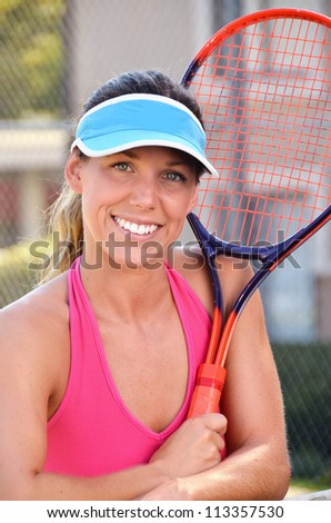 Woman tennis player with racquet/Woman Tennis Player/Physically fit young female tennis player