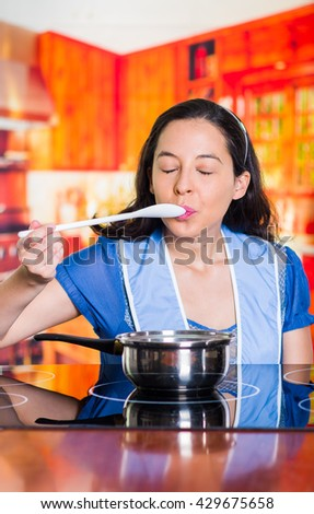 Woman testing a spoon of her preparation, delicious testing face - stock photo