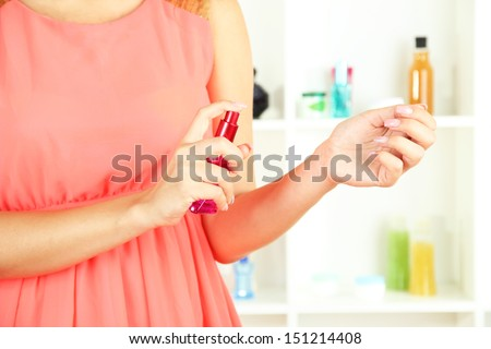 Woman testing perfume on shop windows background