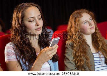 Woman text messaging on her mobile during movie at the cinema - stock photo
