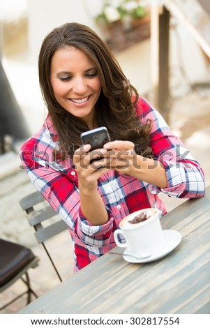 Woman text messaging on mobile phone - stock photo