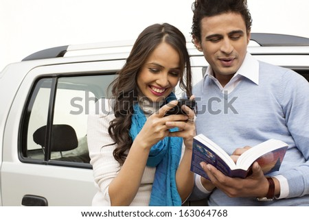 Woman text messaging with a mobile phone and man reading a book - stock photo