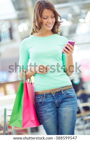 Woman texting a message in shopping mall