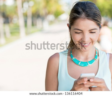 Woman texting from her mobile phone outdoors - stock photo