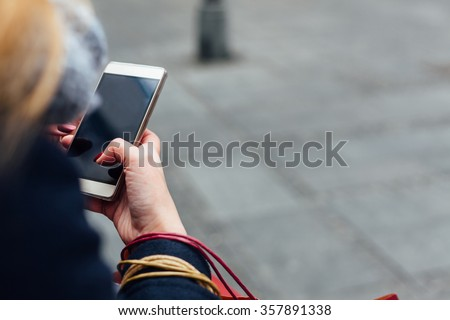 Woman texting message on her mobile phone outdoors - stock photo