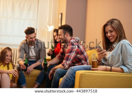 Woman texting on a mobile phone at home party. - stock photo