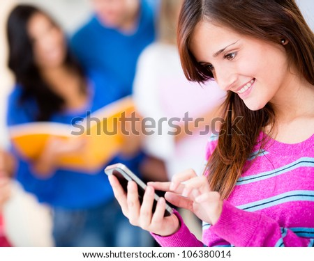 Woman texting on her cell phone and smiling - stock photo